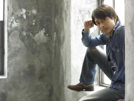 窓辺に座る吉田栄作